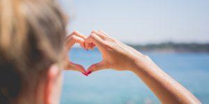 Hand in heart shape by sea